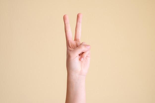 Mão fazendo sinal de vitória em fundo amarelo