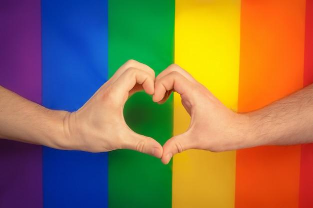 Mão, fazendo um sinal de coração com bandeira do arco-íris de orgulho lgbt