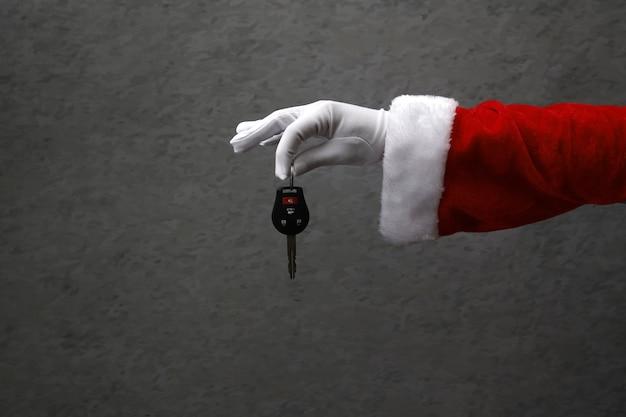 Mão fechada com luva de papai noel segurando a chave do carro.