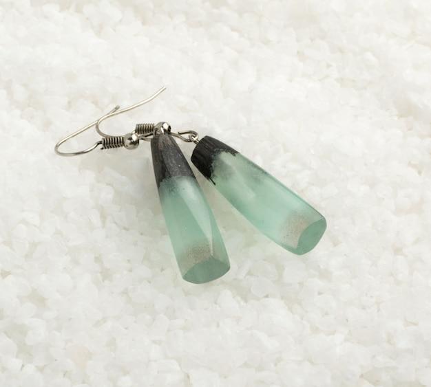 Mão feita de brincos de água-marinha verde claro sobre fundo de cristal branco. bijuteria feita de resina epóxi e madeira