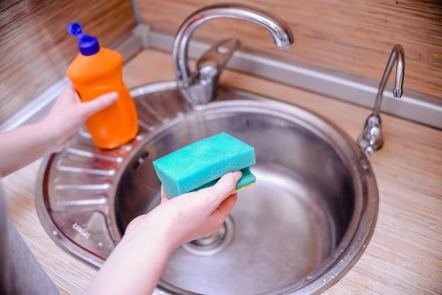 Mão fêmea com a esponja do prato com sabão da lavagem da louça. conceito de limpeza da casa.
