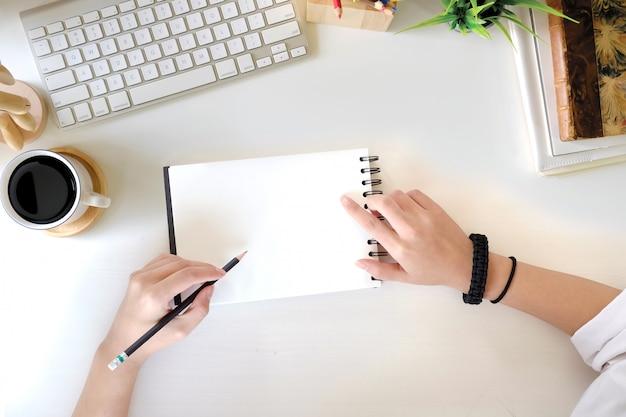 Mão fêmea da vista superior que escreve o caderno vazio na mesa de escritório e no computador brancos com materiais de escritório. conceito de espaço de trabalho