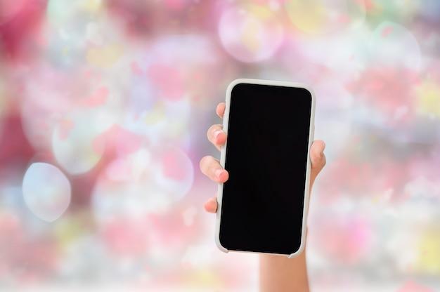 Mão fêmea do close up que mostra a tela em branco do smartphone com fundo da cor do rosa do borrão, espaço da cópia.