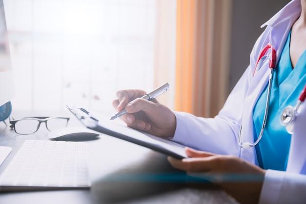Mão fêmea do doutor que guarda a lista de verificação na tabela do escritório com computador. conceito de saúde.