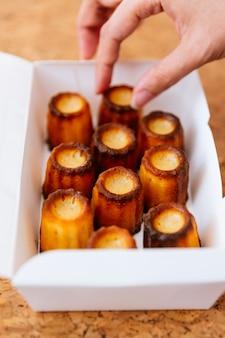Mão fêmea que escolhe canelés cozido fresco dentro da caixa de papel branco.