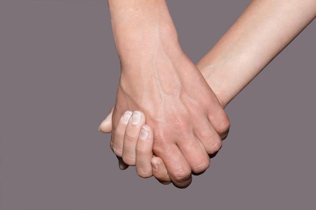 Mão fêmea que guarda a mão masculina no fundo.
