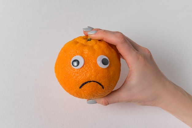 Mão fêmea que guardara um sorriso alaranjado no fundo branco. laranja com olhos e sorriso triste.
