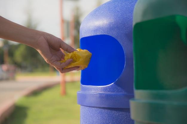 Mão fêmea que joga o plástico amarelo amarrotado na lata de lixo plástica azul.