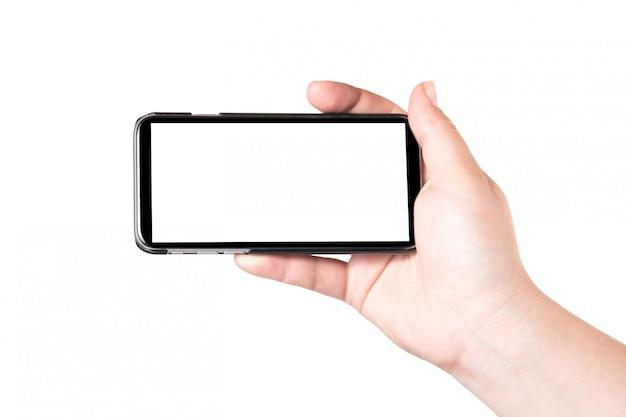 Mão fêmea que mantem o telefone esperto móvel isolado no fundo branco. tela branca em branco.