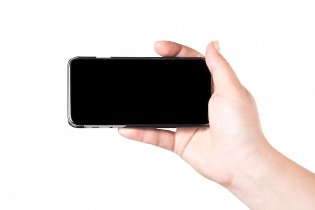 Mão fêmea que mantem o telefone esperto móvel isolado no fundo branco.