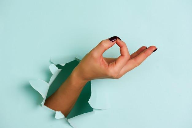 Mão fêmea que mostra o gesto perfeito, sim contra o fundo azul.