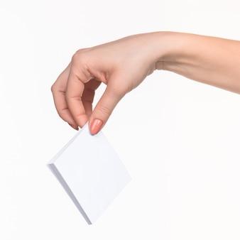 Mão fêmea que prende o papel em branco para registros no branco.