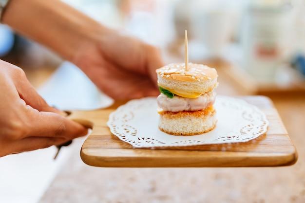 Mão fêmea que serve o mini burger da galinha na placa de desbastamento de madeira com fundo do borrão.