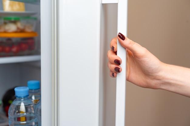 Mão feminina abre porta de uma geladeira