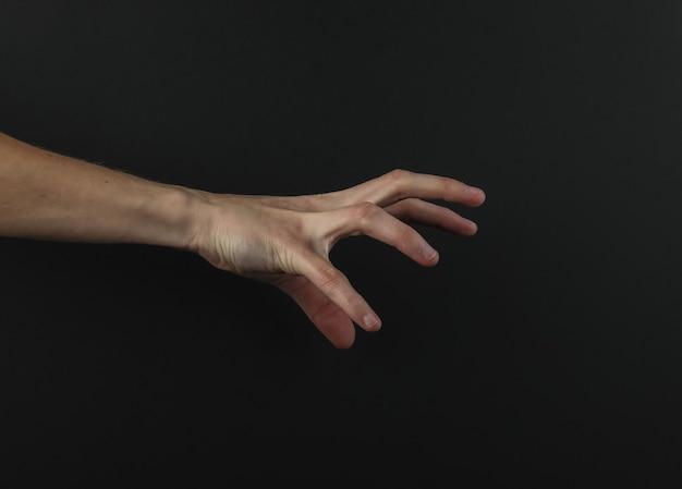 Mão feminina alcança algo em um fundo preto