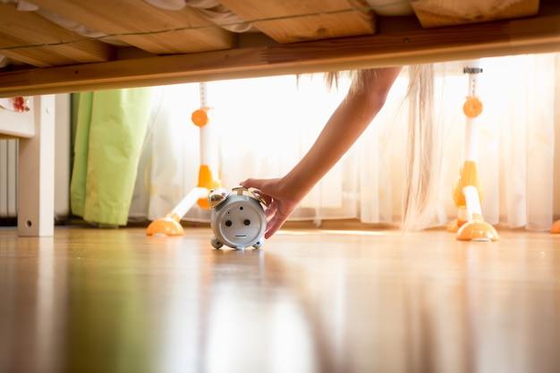 Mão feminina alcançando debaixo da cama o despertador