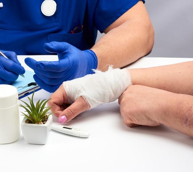 Mão feminina amarrada com uma atadura de gaze branca, uma consulta com um traumatologista