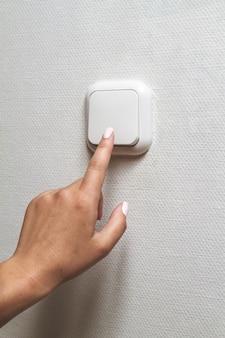 Mão feminina apaga a luz dentro de casa. economia de energia elétrica