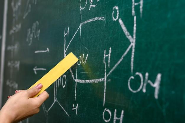 Mão feminina apontando para a fórmula química no quadro-negro close-up