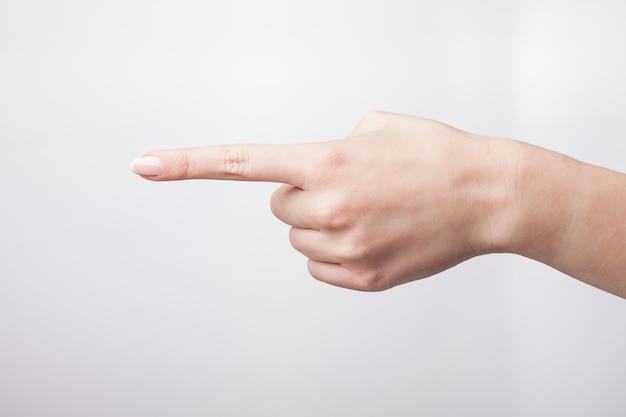 Mão feminina apontando para o espaço vazio.