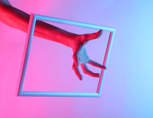 Mão feminina através de uma moldura elevada com luz holográfica neon