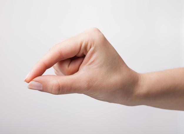 Mão feminina bem cuidada medindo itens invisíveis, gesto feminino com a palma da mão