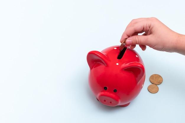 Mão feminina branca coloca uma moeda em um cofrinho vermelho ao lado de moedas de mentira
