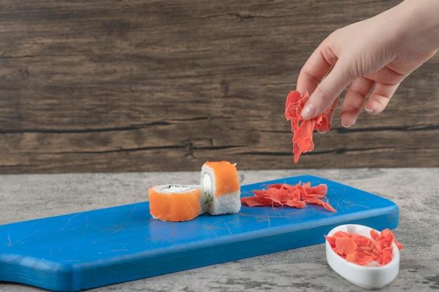 Mão feminina colhendo gengibre em conserva da tábua de corte azul