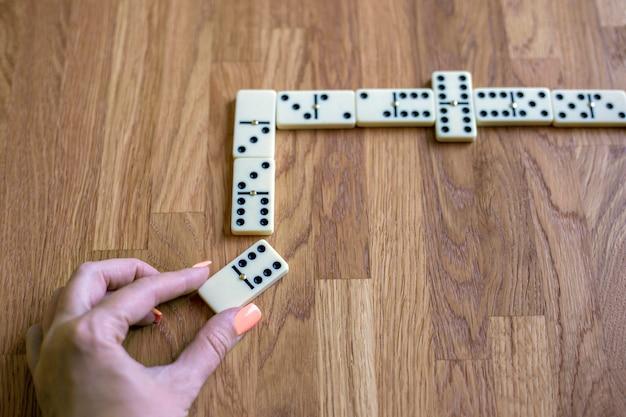 Mão feminina coloca o osso de dominó em uma linha de visão superior jogando o jogo de mesa de dominó