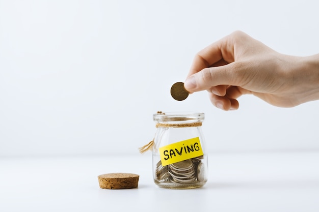 Mão feminina coloca uma moeda em uma jarra com a inscrição saving isolado no fundo branco.