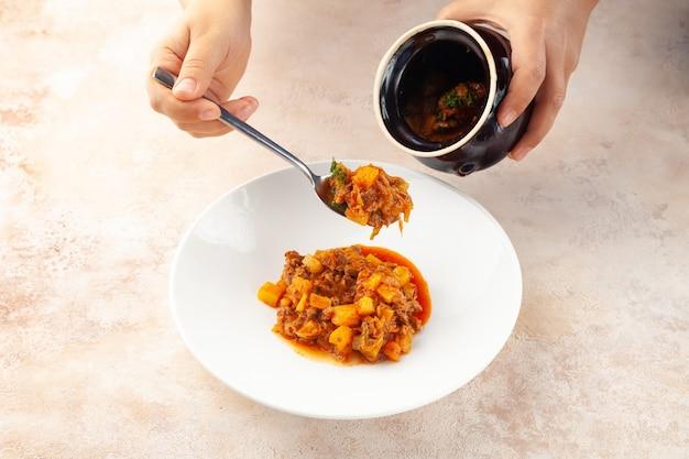 Mão feminina colocando goulash, legumes cozidos e carne