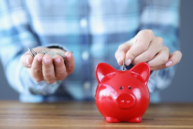Mão feminina colocando moedas no cofrinho