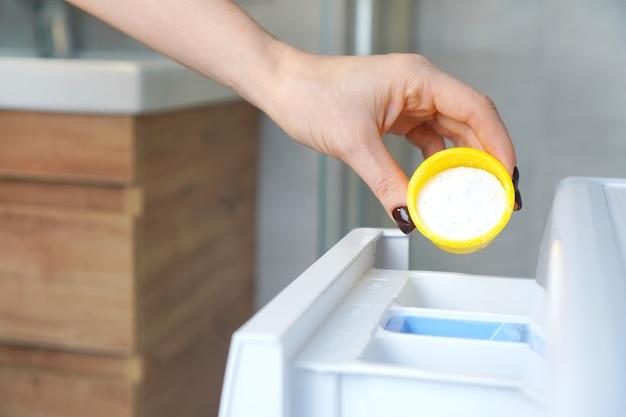 Mão feminina colocando o sabão em pó na gaveta da máquina de lavar