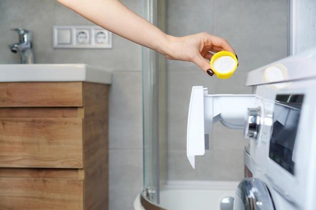 Mão feminina colocando sabão em pó na gaveta da máquina de lavar