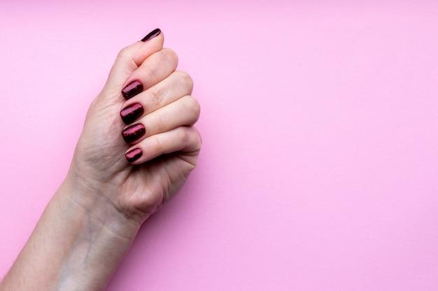 Mão feminina com bela manicure - unhas vermelhas escuras brilhantes em fundo rosa com espaço de cópia