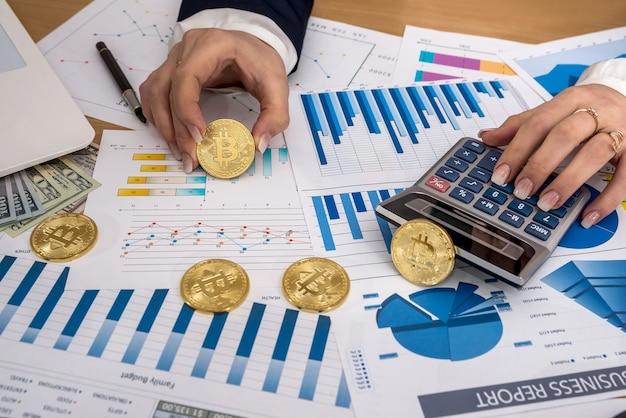 Mão feminina com bitcoin e gráfico de negócios