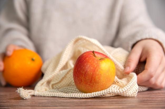 Mão feminina com bolsa de rede ecológica para fazer compras com frutas frescas
