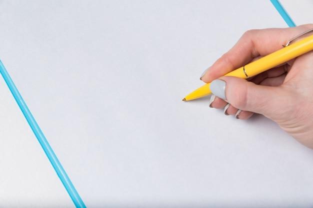 Mão feminina com caneta em uma folha de papel em branco