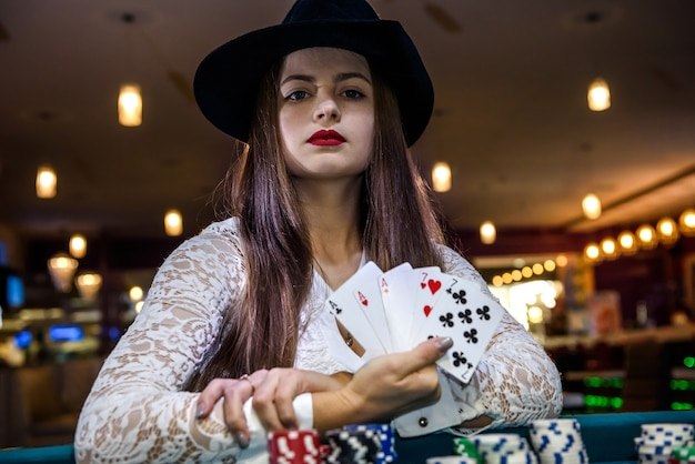 Mão feminina com cartas de jogar e fichas de pôquer de perto