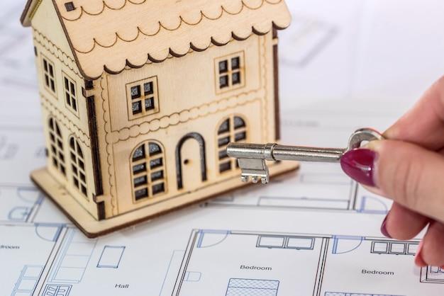 Mão feminina com chave e modelo de casa de madeira no plano