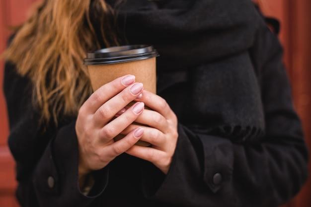 Mão feminina com copo de papel de café para viagem