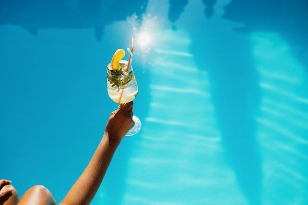 Mão feminina com coquetel fresco, piscina no fundo