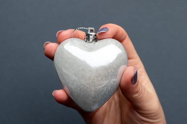 Mão feminina com coração de prata brilhante sobre fundo cinza turva. foco seletivo. vista de perto