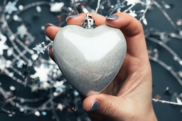 Mão feminina com coração de prata brilhante.