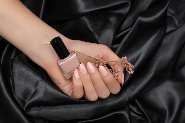 Mão feminina com desenho de unhas rosa segurando verniz vermelho claro em tecido preto.