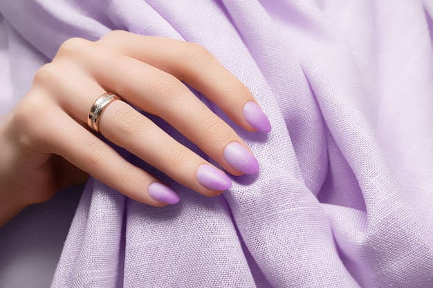 Mão feminina com desenho de unhas roxas na superfície do tecido roxo.