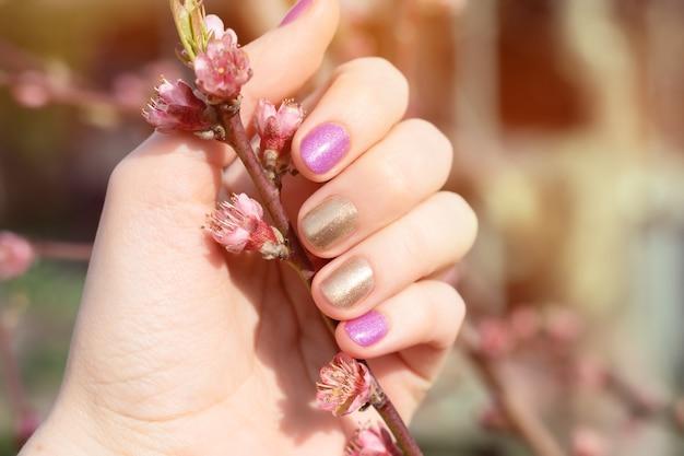 Mão feminina com design de unha ouro e roxo, segurando o ramo de flor.