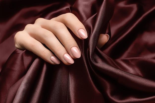 Mão feminina com design de unha rosa na superfície do tecido escuro.