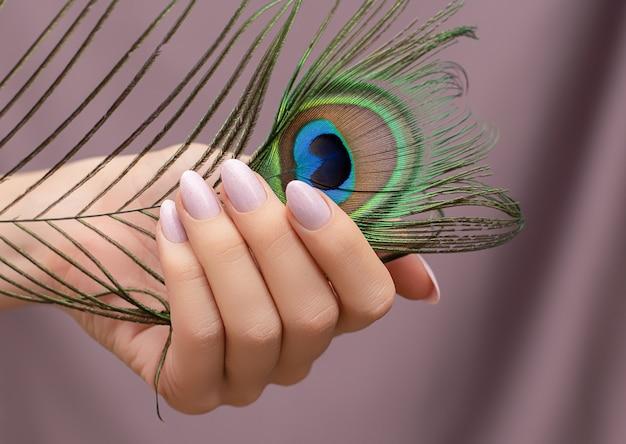 Mão feminina com design de unha rosa segurando pena de pavão.