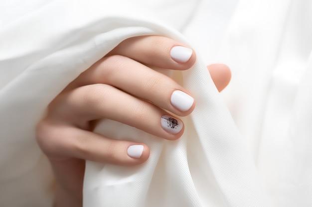 Mão feminina com design de unhas brancas, close-up.